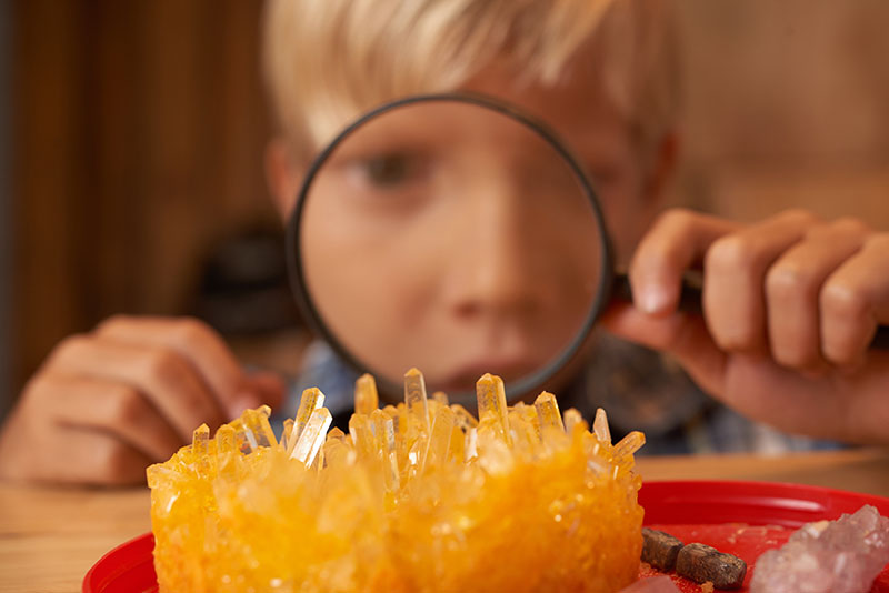 Boy looking on crystals he grew through magnifying glass