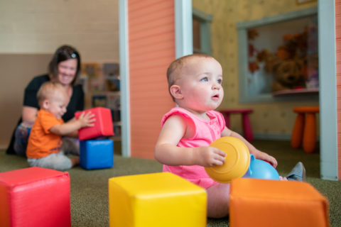 Infant in pink outfit staring in wonder and playing with blocks in totopia