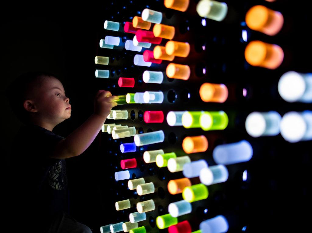 child playing with light up wall