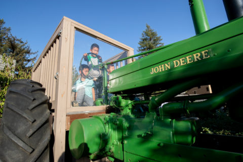 two children safely playing and experiencing hands-on a real tractor