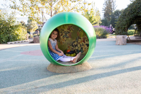 Child sitting inside green butterfly ball statue