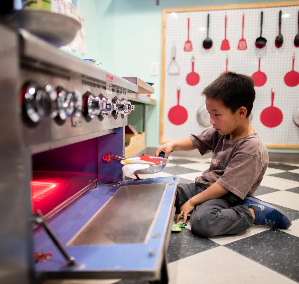 children playing with pretend oven