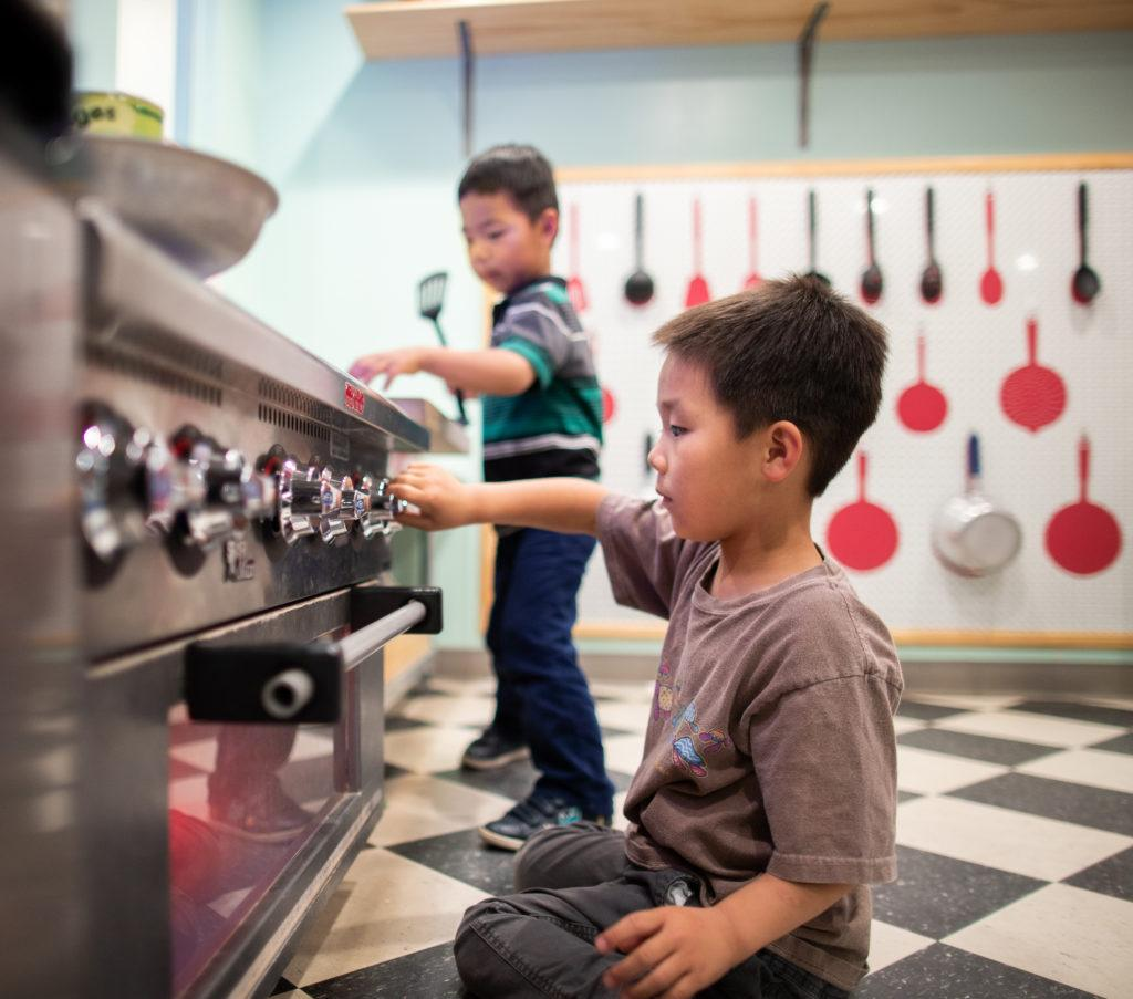 children playing with oven in pretend kitchen