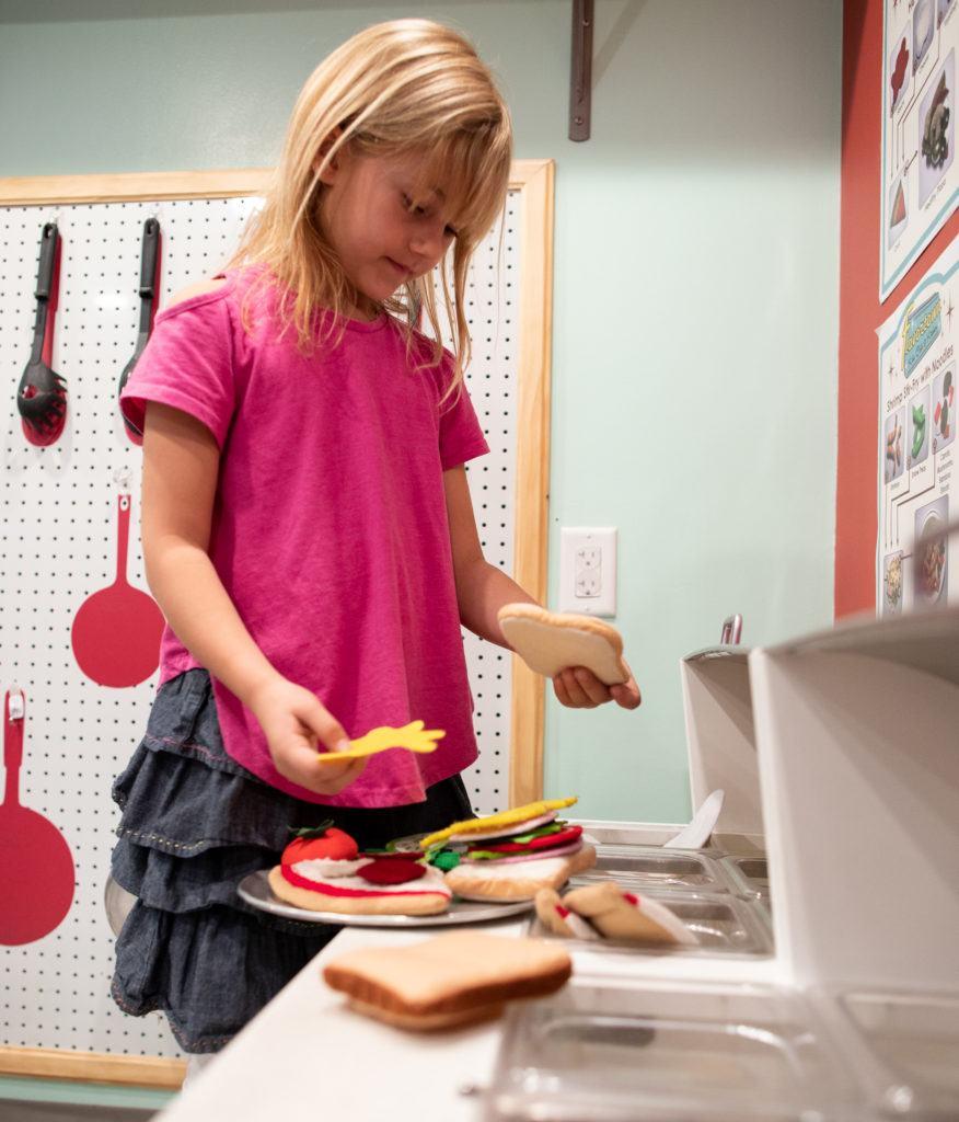 child making sandwiches from felt