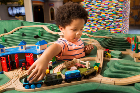 child playing at mini train town