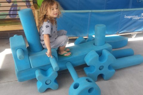 child playing in blue blocks area