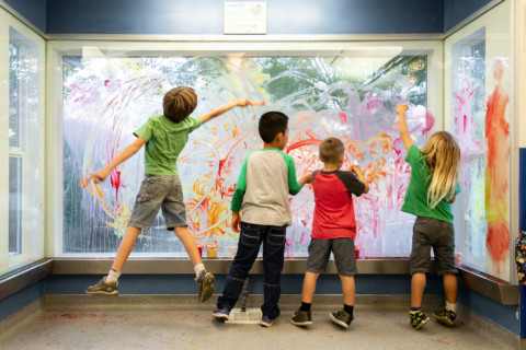 several kids playing at paint window