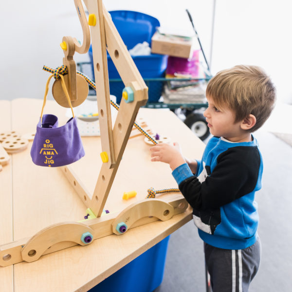 child playing with wood crane