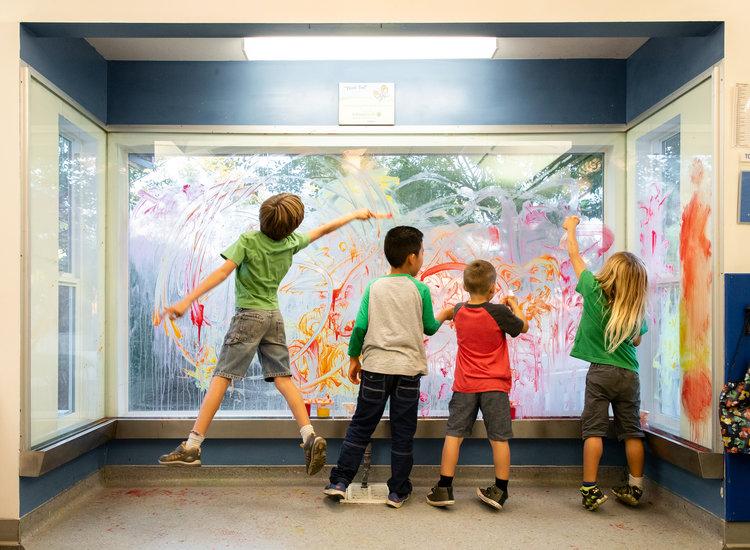 Children finger painting on window