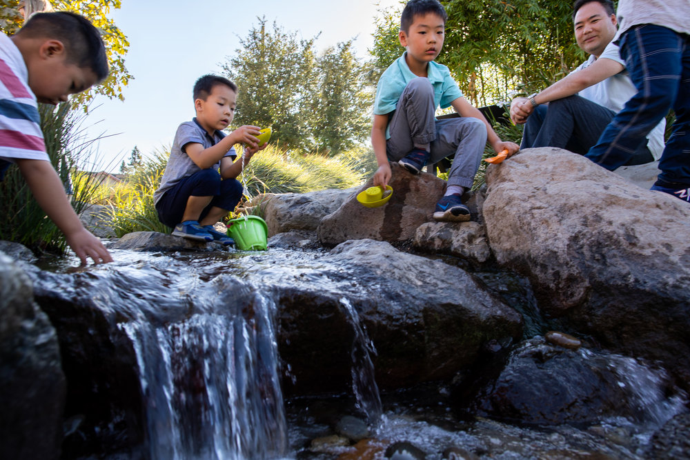 children playing on rocks in creek play area