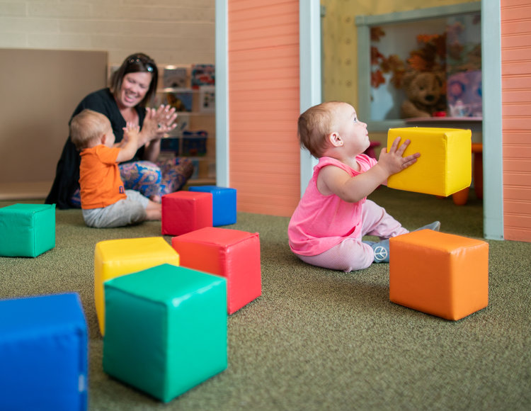 little girl in pink playing with blocks near adult and child
