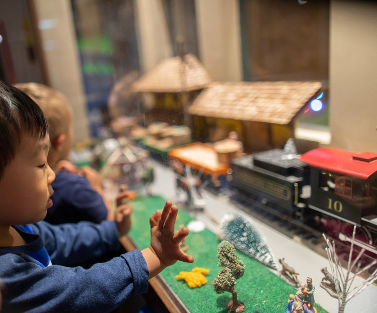 two kids admiring toy trains through a glass partition