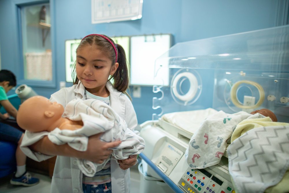 young girl playing doctor in medical lab playroom