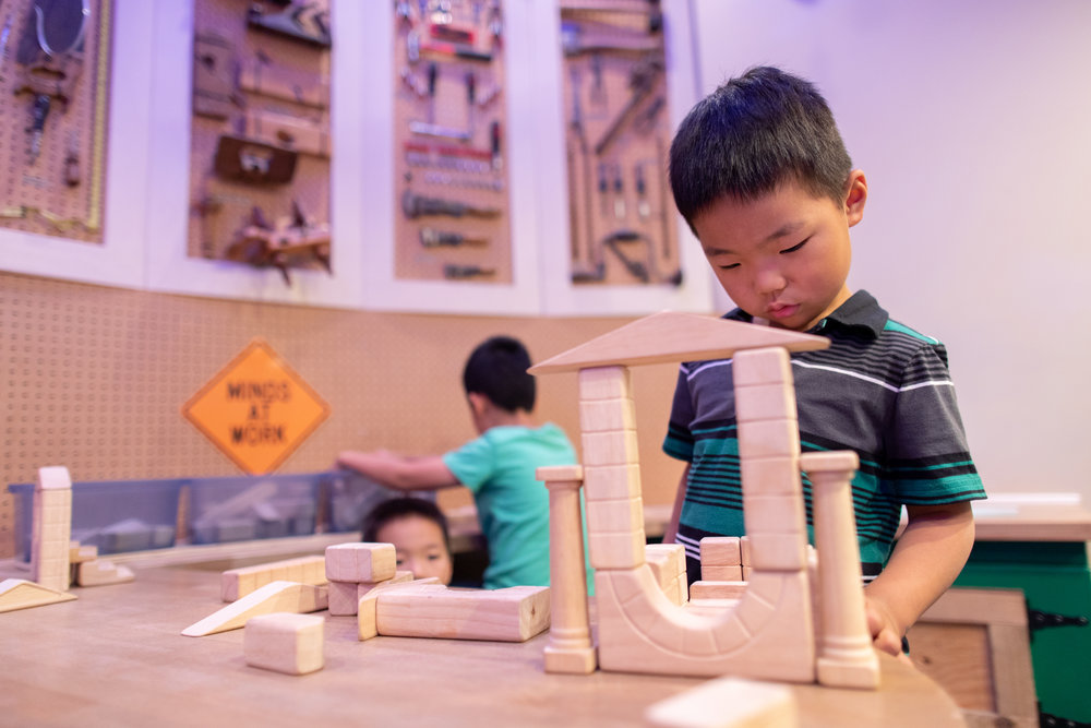 young boy looking at wooden blocks in construction play area