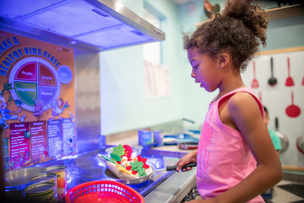 child wearing pink shirt and playing in kitchen play exhibit
