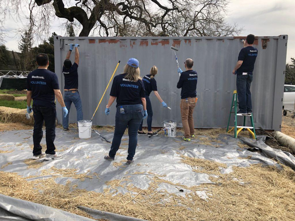volunteers painting cargo container