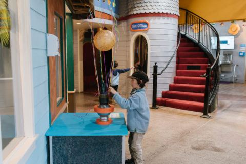 Child playing with Bernoulli Blower exhibit