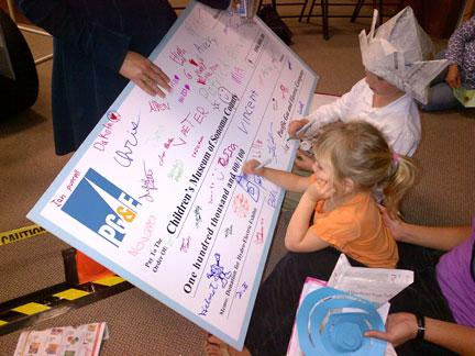 large check being drawn on by children