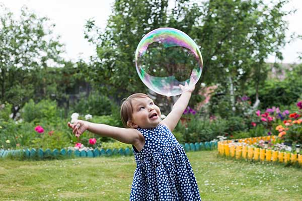 little girl is playing with big bubbles in the backyard