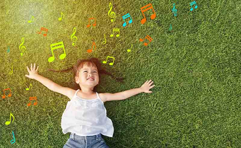 little girl smile and lay on grass with music note background