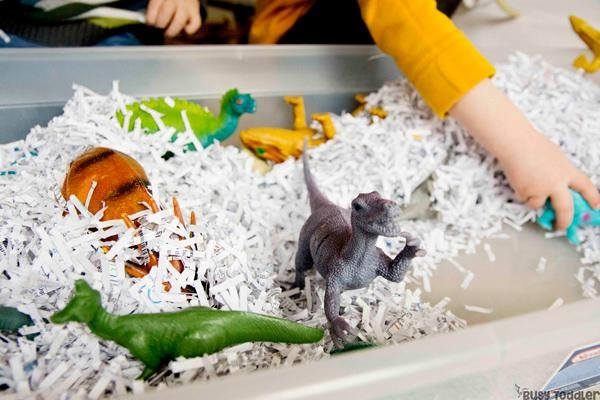 toddler playing with shredded paper in a bin full of dinosaur toys as a sensory activity