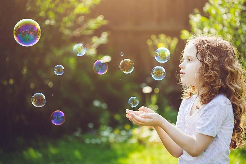 little girl catching bubbles in the backyard