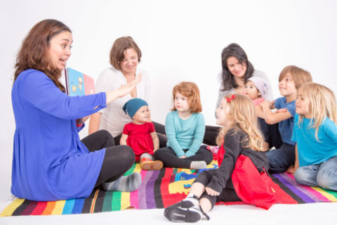 children gathered around a teach reading a book in Spanish