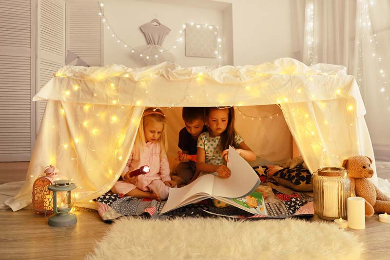 children playing in a blanket fort in their living room