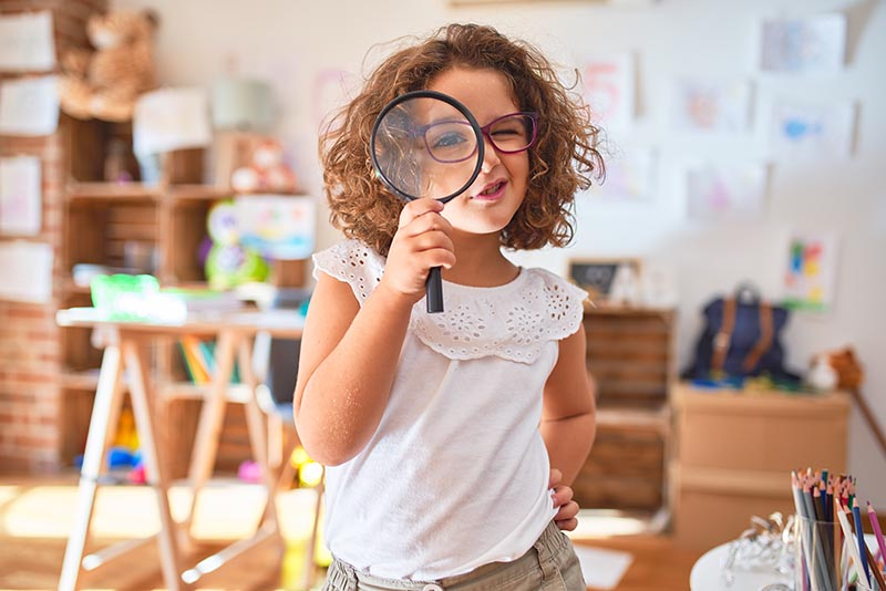 young child in home looking for something with a magnifying glass