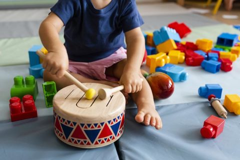 toddler playing with a drum and having fun