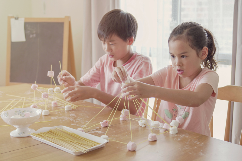 two kids using marshmallows and skewers in science experiment