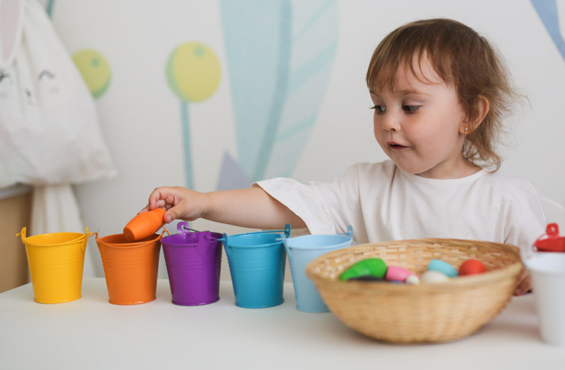 toddler sorting colored objects into cups