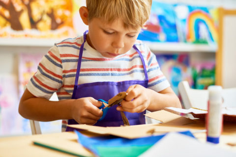 young boy using scissors for a paper craft project