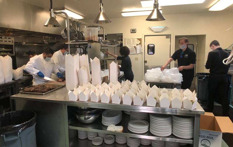 crew packing meals to go in paper containers in kitchen