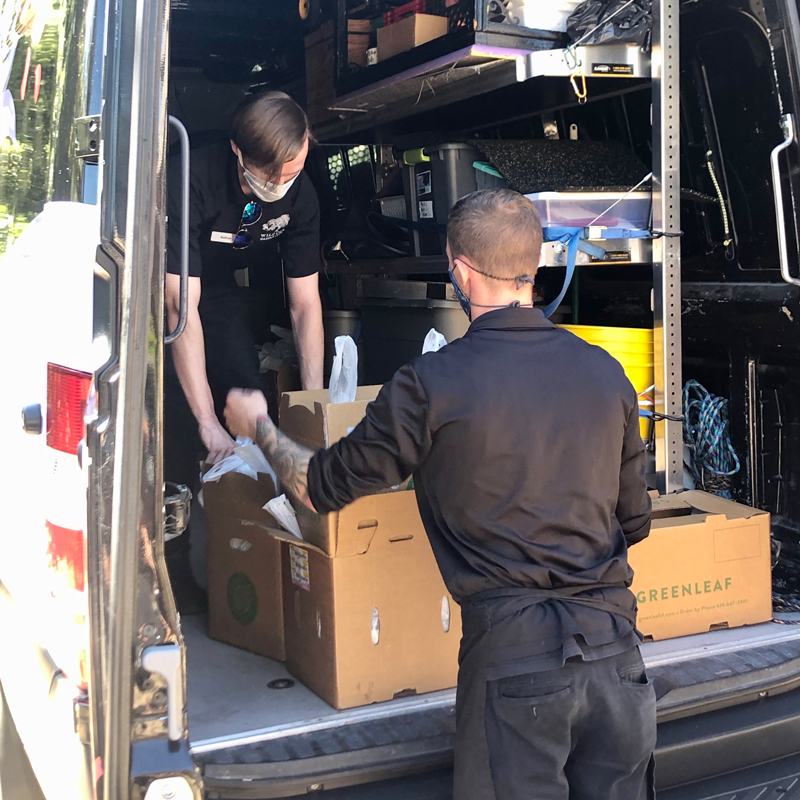 two adults loading boxes into a van
