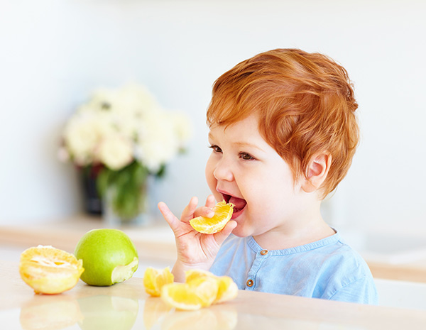 young redheaded child taste testing sour fruits for sensory activity play