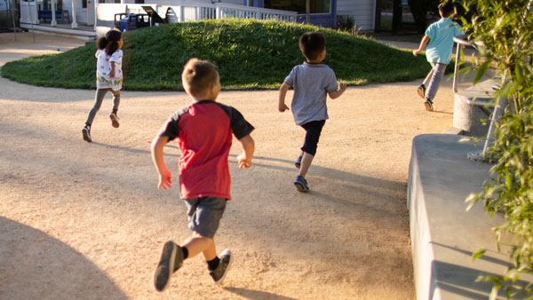 young boys running around outside at the childrens museum of sonoma county