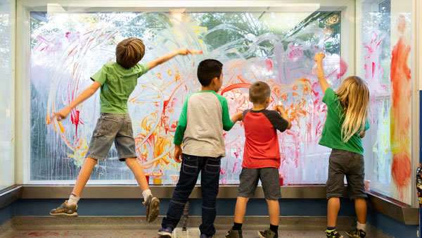 four young boys painting on an art window