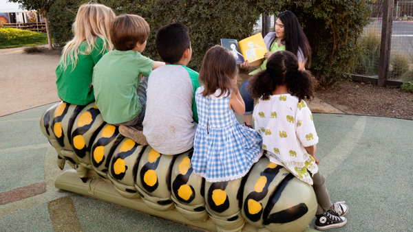5 young children sitting on a large caterpillar bench at the Children's Museum of Sonoma County listening to a story being read aloud by an adult sitting in front of them
