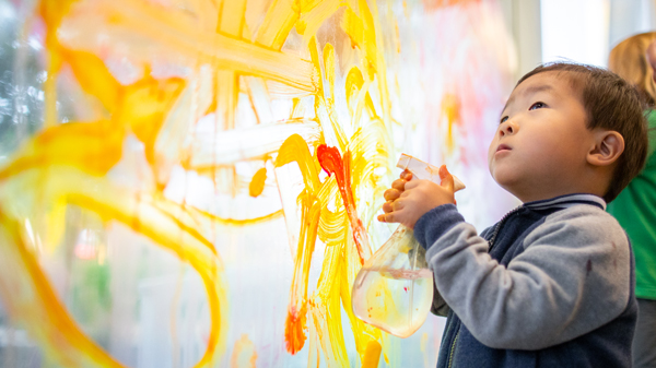 A small child playing with a spray bottle in the interactive art wall at the Children's Museum of Sonoma County