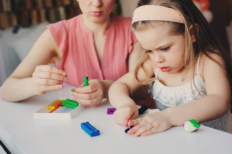 woman observing her child play with playdough