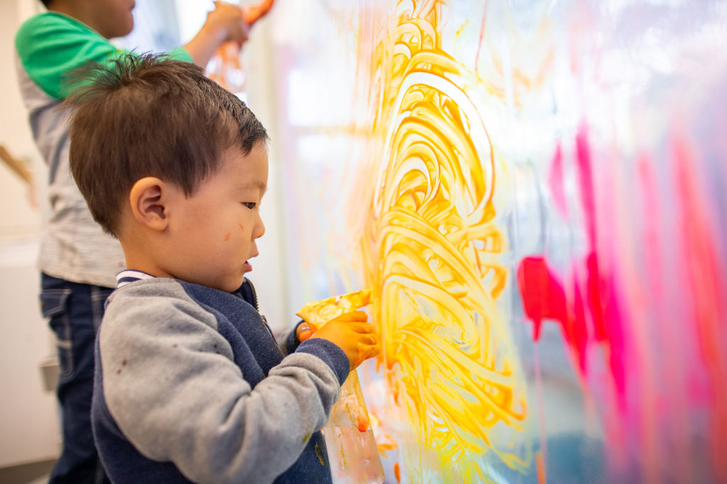 small child finger painting yellow on window