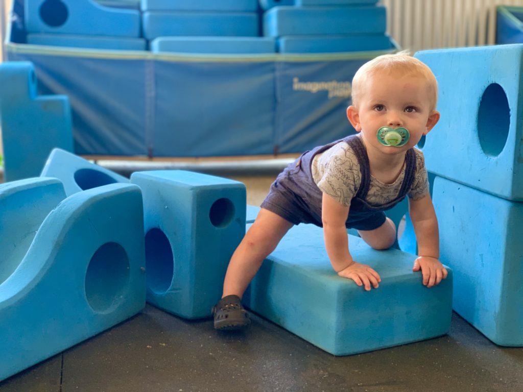 toddler playing on blue blocks