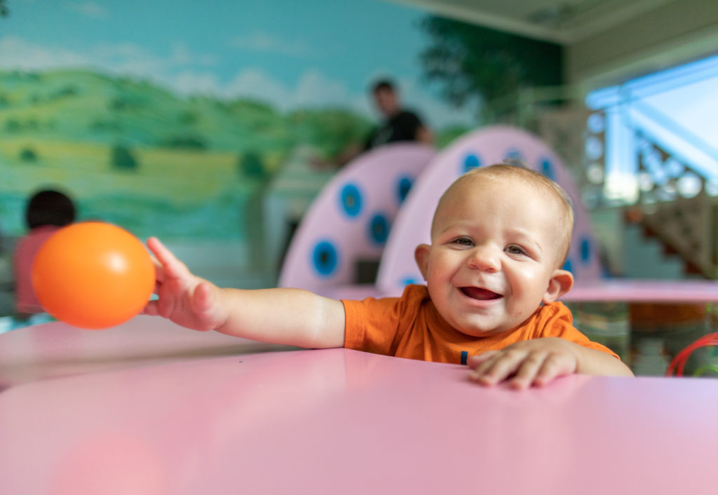 Infant playing with an orange ball in Totopia