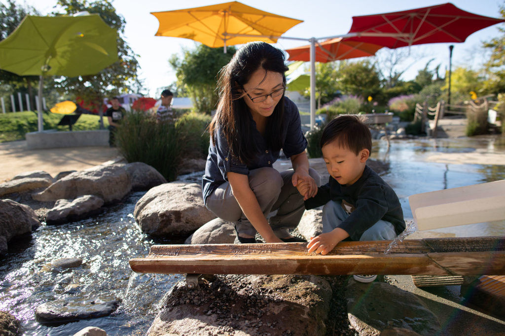 Parent and child playing with water in creek play area