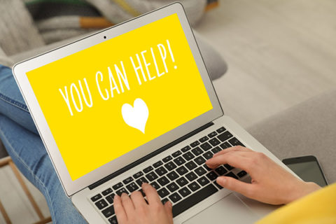 Donations concept. Woman holding laptop with text YOU CAN HELP indoors, closeup
