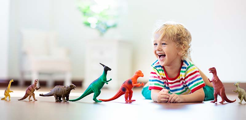 very happy child playing with colorful toys