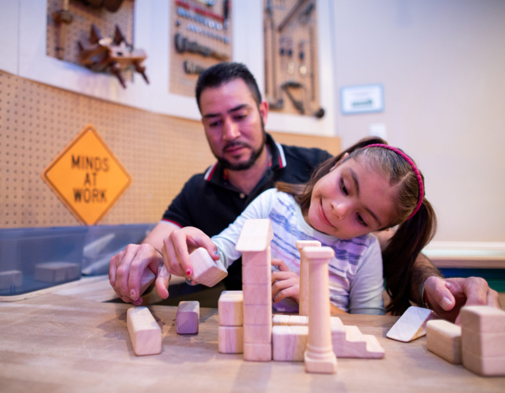 Parent and child playing with wood blocks