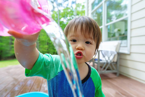 Young toddler boy playing with water outside