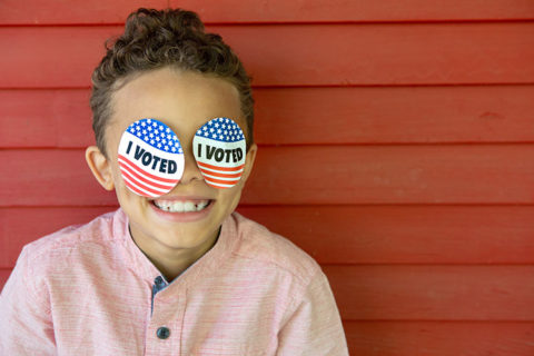 young child smiling wearing I Voted stickers on his face